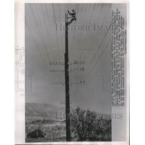 1962 Press Photo A workman attaches a nuclear bomb explosion detector on a pole