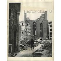 1948 Press Photo Polish Woman Walks & Picks Through Cluttered Courtyard