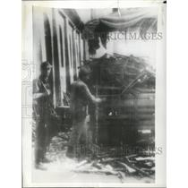 1943 Press Photo Soldier Keeps His Gun Over Shoulder as an Italian Loads Rifles