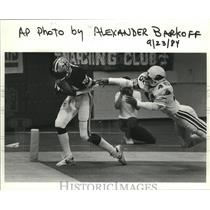 1984 Press Photo New Orleans Saints Player Avoiding Diving Cardinals Player