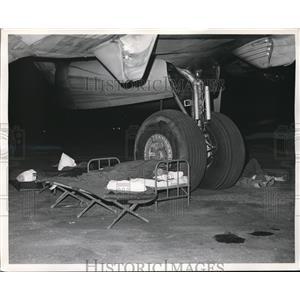 1960 Press Photo Air Force Crew sleep on the ground wheel of C-124 Globemaster.