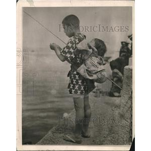 1920 Press Photo Japanes boy & baby on his back fish at a shoreline