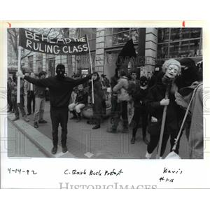 1992 Press Photo A Masked Demonstrator Holds Up a Sign Outside Hilton Hotel