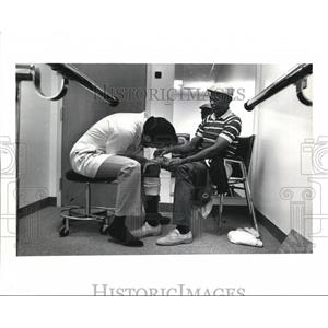 1991 Press Photo Thomas checks the adjustments on Raymond Hurd's limb