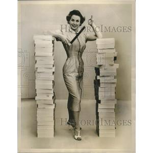 1955 Press Photo Model Stands In Between The Stacks Of Film - nef69346