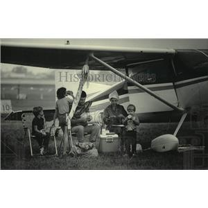 1985 Press Photo Family seeks shelter from rain under wing of plane, Oshkosh