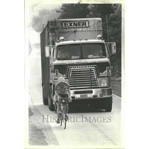 1981 Press Photo Giant Semi Truck Rides Cyclists Tail