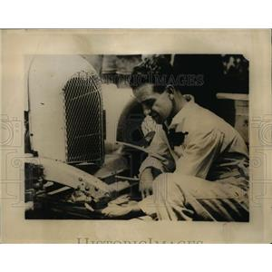 1925 Press Photo race car driver Pete DePaolo tying lucky baby shoes onto car