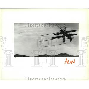 1988 Press Photo John Kazian walking on the wing of an upside-down biplane