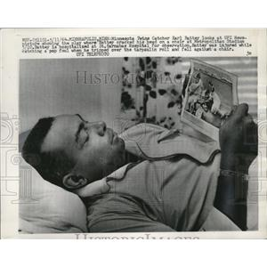 1964 Press Photo Twins catcher Earl Battey looks at UPI photo of his fall.