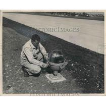 1949 Press Photo Joseph Sanek Inspects Runway Light, Gen. Mitchell Field, Wis.