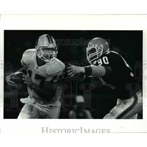 1991 Press Photo Chris Chandler is pressured out of the pocket by Rob Burnett