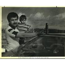 1986 Press Photo Victor Adonie and son Victor Jr. with aircraft debris