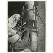 1938 Press Photo J.R. Taylor Cleaning a Furnace in Milwaukee, Wisconsin