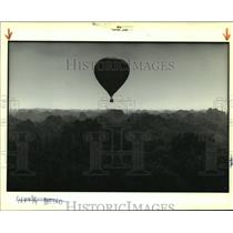 1989 Press Photo A hot air balloon lazily drifts over trees near Baton Rouge