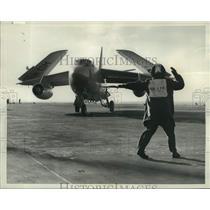1957 Press Photo control man wigwags a Douglas A-30 Skywarrior bomber on deck