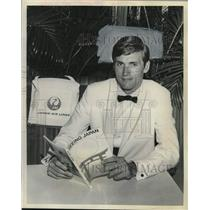 1965 Press Photo Thomas S. Melvin Jr. with travel guide for Japan in New York