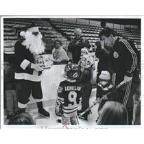 1989 Press Photo Boston Bruins Coach Terry O'Reilly Santa Presents Children