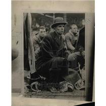 1924 Press Photo Man sitting outside on football helmets
