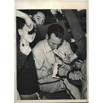 1940 Press Photo Sports star Cunningham signing autographs