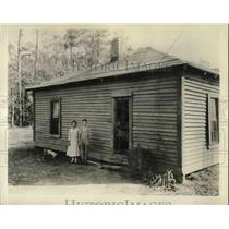 1934 Press Photo couple standing next to one room home in rural hills of Alabama