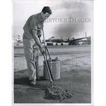 1960 Press Photo Roland T Godslin Airport Employee Cleaning Runway - neb74440