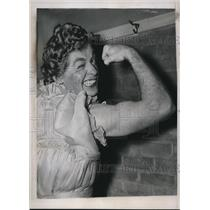1938 Press Photo Jim Walsh flexes his muscles while wearing a dress