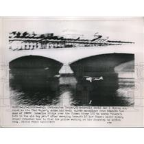 1953 Press Photo Christopher Draper zooms small silver monoplane under bridge