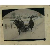 1921 Press Photo Man with a horse-drawn sled transporting supplies