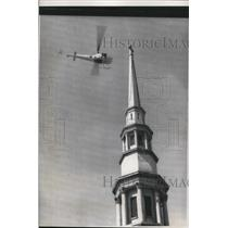 1957 Press Photo A helicopter snare the rope left hanging from a church steeple
