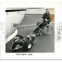 1987 Press Photo Carl Hay while he uses a tow tractor to move his plane