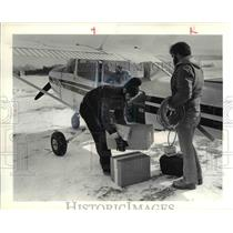 1982 Press Photo Pilot, left, unload cargo after landing at Put In Bay, Ohio