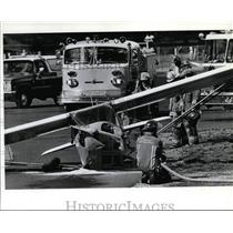 1993 Press Photo Spokane firefighters watch over plane at Felts Field