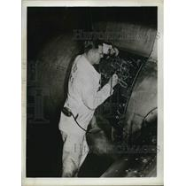 1952 Press Photo United Airlines inspector uses miners lamp to examine repairs