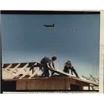 1993 Press Photo Garco crew nails roof while a KC135 circles at Fairchild AFB