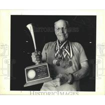 1990 Press Photo Reggie Barris, Senior Olympian, Holds Trophy and Wears Medals