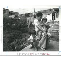1984 Press Photo Dong Van Dong baby-sits at Allen Parkway Village, Houston