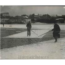 1926 Press Photo Two men with fishing poles ice fishing on a lake - mjx43295