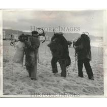 1957 Press Photo Fishermen in Portugal carry tackle on their way home