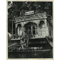 1952 Press Photo Boatman vendor delivers flowers to European renter of houseboat