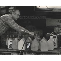 1985 Press Photo Harold Cooper fills jugs with water, Jefferson County, Alabama