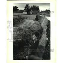 1993 Press Photo Mrs. Reni Bloch next to fence falling due to erosion, Metairie
