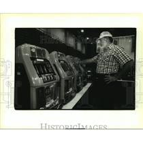 1994 Press Photo Jim Cooper puts quarter in an old slot machine - nob22931