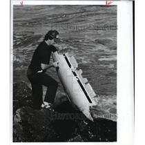 1989 Press Photo Kim Bevers pulls helicopter part from Gulf of Mexico in Texas