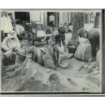 1968 Press Photo Vietnamese fill sandbags for bunkers at their homesin Saigon