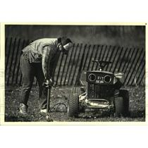 1986 Press Photo Lawn mower racer pumps up his mower tires before race