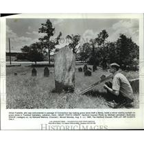 1985 Press Photo Alfred Fredette casts sunlight on Trumbull Cemetery gravestone