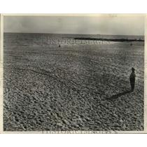 1962 Press Photo Officer Villani surveys tracks left by swimmers now barred.