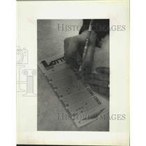 1992 Press Photo Lori Banks scratches off her number in opening of lotto game