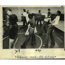 1978 Press Photo Class members practice using umbrella to keep attacker away